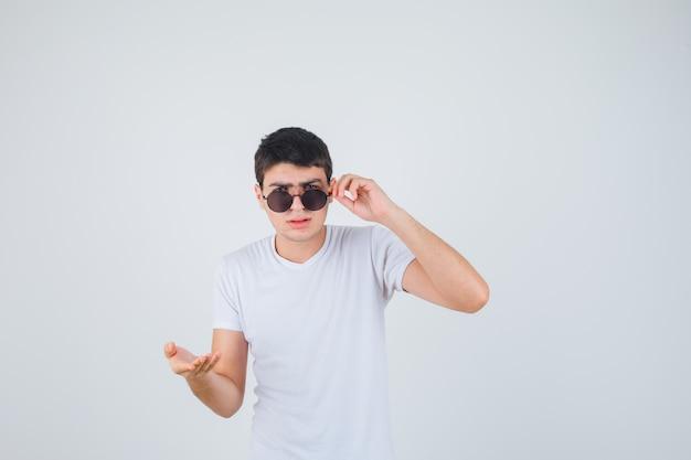 Молодой мальчик протягивает руку в вопросительном жесте в футболке и выглядит серьезно. передний план.