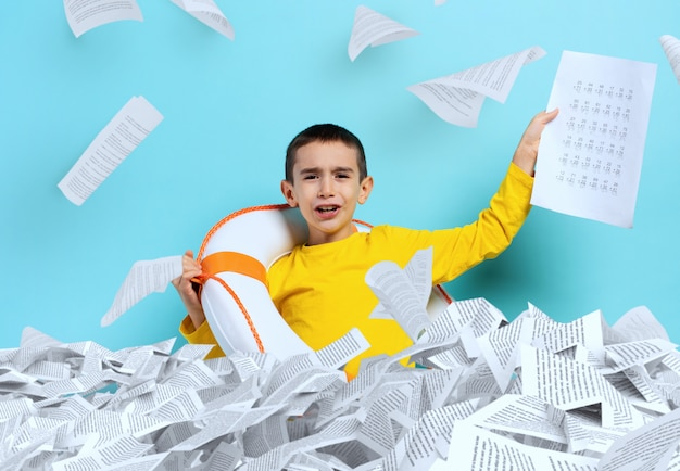 Young boy student is drowning in a sea of sheets of exercises. cyan background