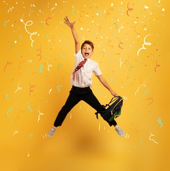Молодой мальчик-студент высоко прыгает, довольный продвижением по службе с отличием