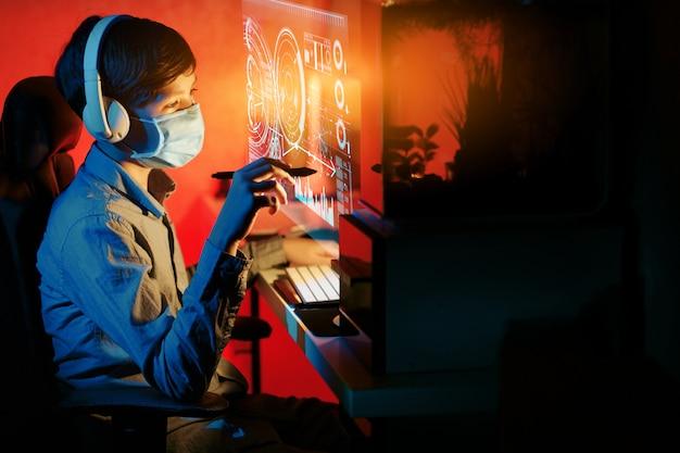 コロナウイルスの検疫中に自宅でオンラインコースを勉強している少年。遠隔教育のコンセプトです。