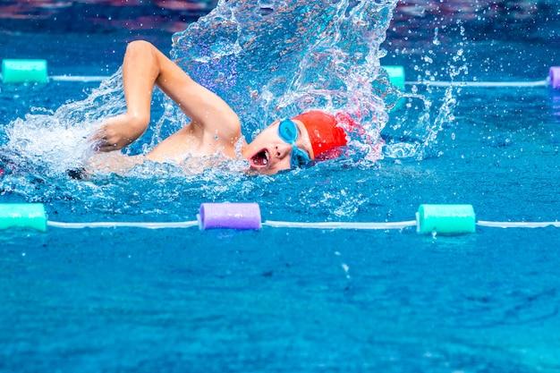 地元のプールでフリースタイルのストロークを練習している若い少年の泳者