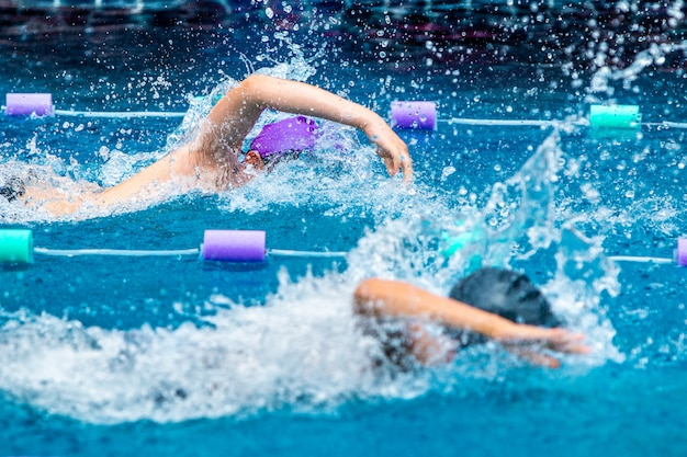 Young boy swimmers racing in freestyle