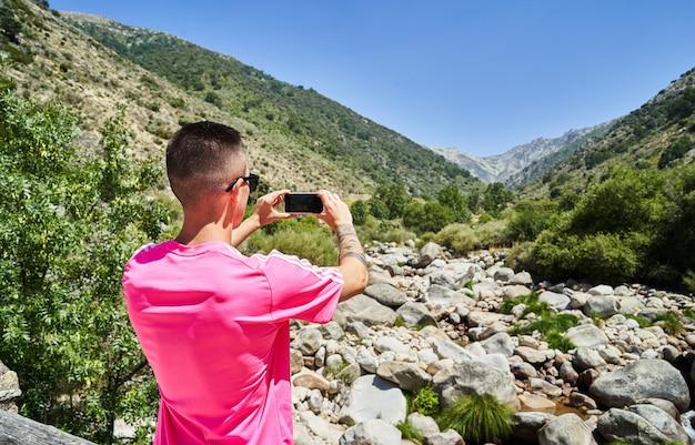 山のある風景に携帯で写真を撮る少年。