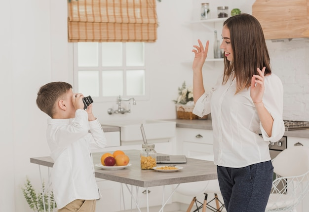 Young boy taking a picture of his mother