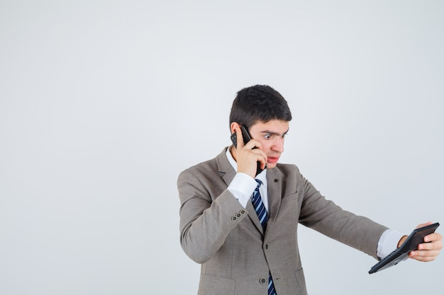 Young boy talking to phone, looking at calculator in formal suit and looking surprised. front view.