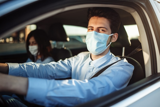Young boy taxi driver gives passenger a ride wearing sterile medical mask.