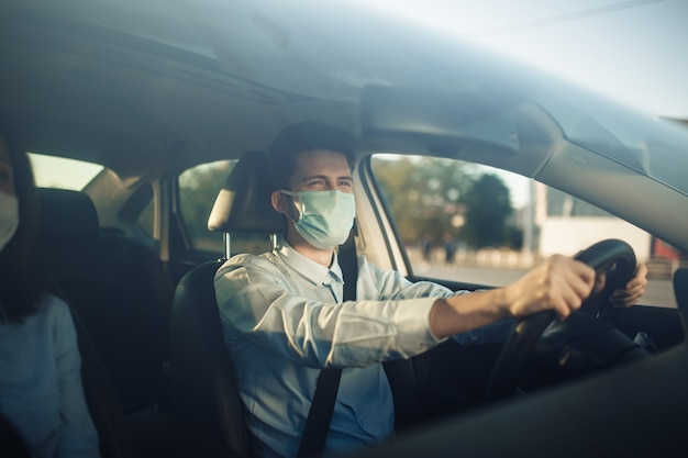 Young boy taxi driver holds his hands on the steering wheel and wears sterile medical mask.