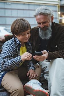 スマートフォンでインターネットを使用して祖父を教える少年