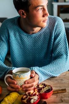 家の外を見てティーカップを持っていると思う10代の少年-秋の孤独とうつ病の概念の人々を屋内で-青いセーターを着た白人男性