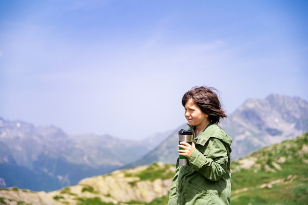 Young boy of ten years old staying in a mountains, holding travel tumbler and drinking tea. child hiking in the highlands.  kid looking aside and admiring wild nature.