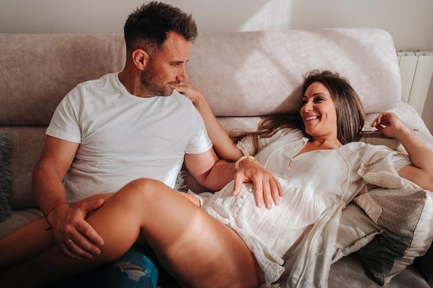 소파에서 웃고 있는 서로를 바라보면서 아내의 임신한 배를 만지는 어린 소년