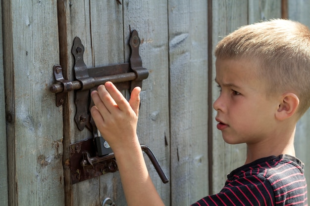 Young boy trying to open rusty slide bolt lock