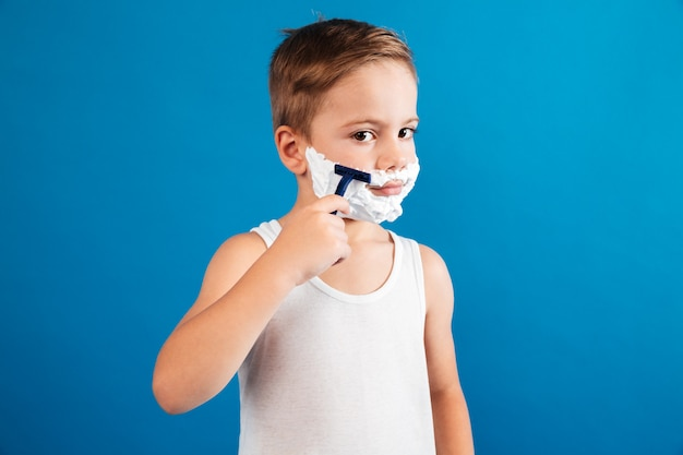 Young boy trying shaving his face like man