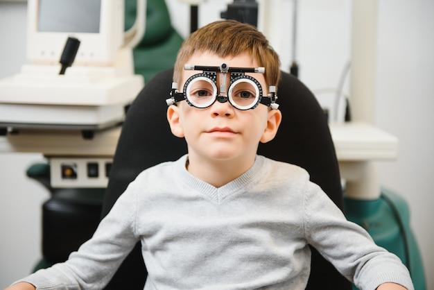 Молодой мальчик проходит проверку зрения с очками в медицинской клинике