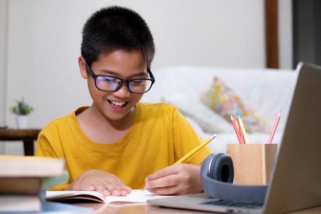 Young boy using computer and mobile device studying online. education and online learning.