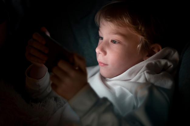밤에 침대에서 스마트 폰을 사용 하여 어린 소년