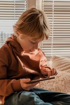 ベッドでスマートフォンを使用して少年
