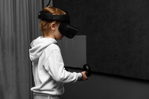 Young boy using virtual reality headset with copy space