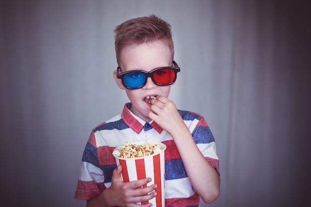 어린 소년은 영화관이나 집에서 3d 안경으로 영화를 본다.