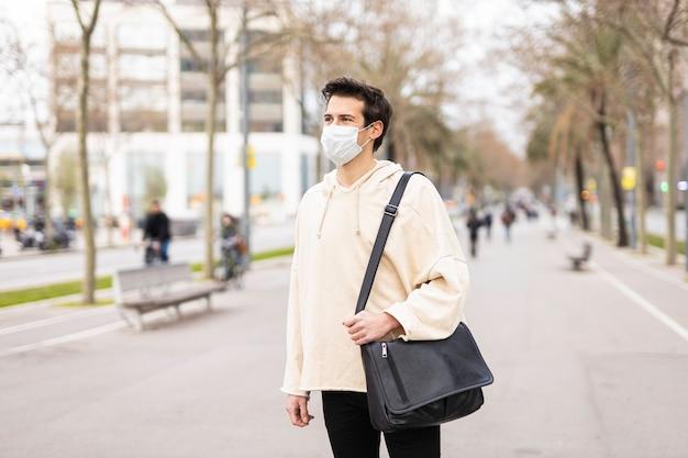 通りでマスクを身に着けている少年
