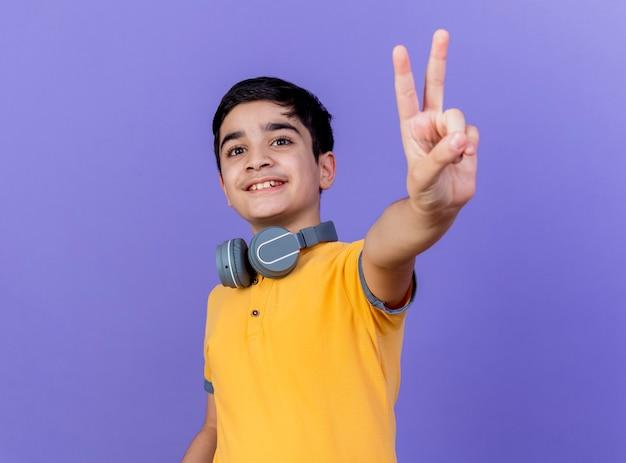 Ragazzo che indossa le cuffie sul collo isolato sulla parete viola