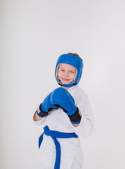 Young boy wearing a helmet and boxing gloves in a white uniform on a white wall