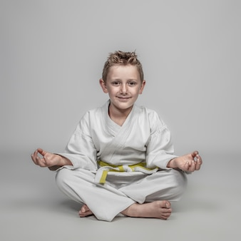 Young boy wearing martial arts costume meditating