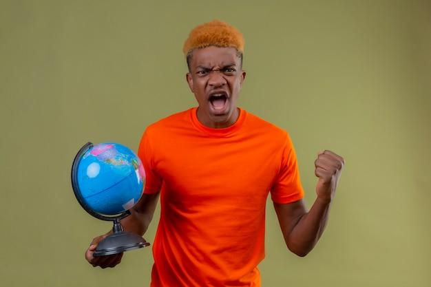 Молодой мальчик в оранжевой футболке держит глобус в кулаке, кричит с сердитым выражением лица, стоя над зеленой стеной