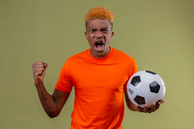 Young boy wearing orange t-shirt holding soccer ball clenching fist shouting with angry expression on face standing over green wall