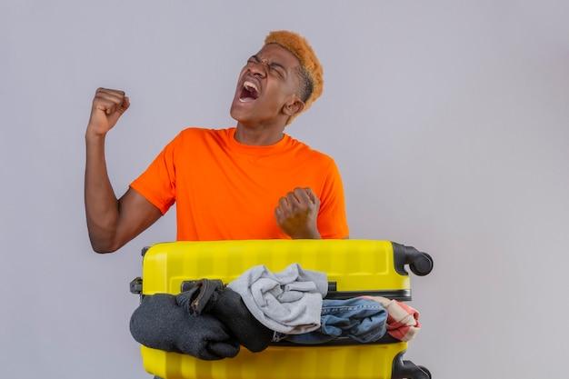 Giovane ragazzo che indossa la maglietta arancione in piedi con la valigia da viaggio piena di vestiti pazzi e pazzi alzando i pugni gridando frustrato sul muro bianco