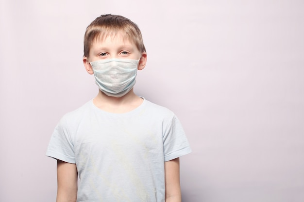 Young boy wearing protection face mask against coronavirus. corona virus and symptoms of an epidemic virus. copy space.