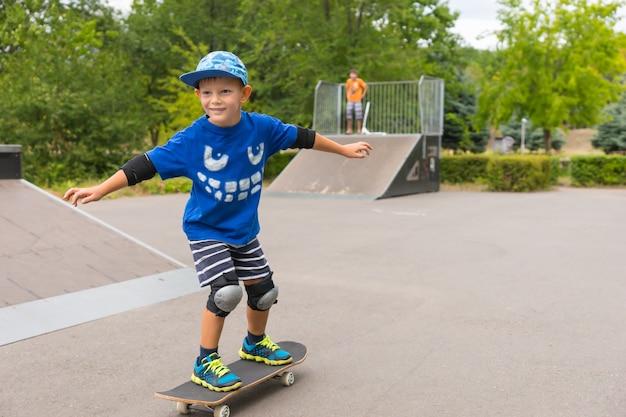 夏休みを楽しんでいるスケートパークで彼のスケートボードに乗って保護膝と肘パッドとトレンディな青い服を着ている少年