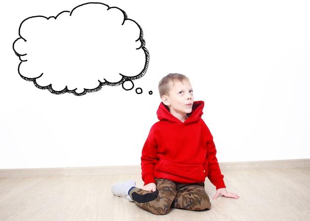 赤いパーカーを着ている少年は、何か、あなたのテキストのためのスペースを持つテキストクラウドについて考えて空想にふけっています。子供のファンタジーと夢のコンセプト。吹き出し。