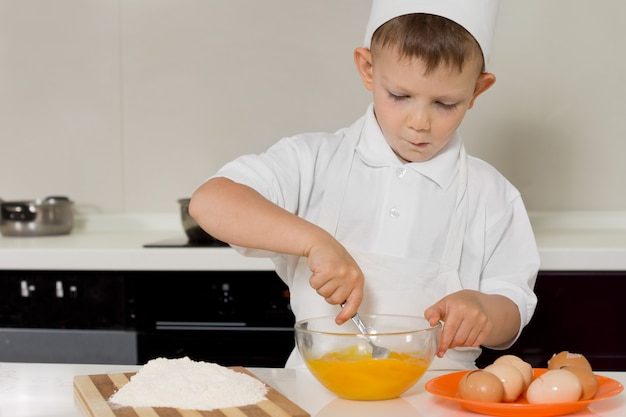 Young boy whisking eggs with a fork