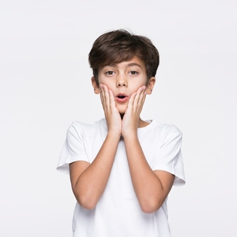 Young boy on white background surprised