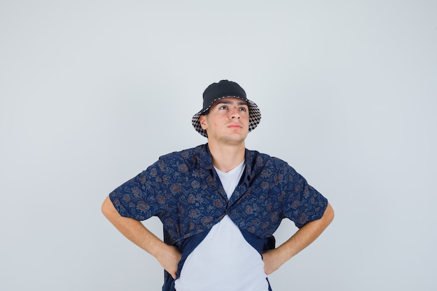 Young boy in white t-shirt, floral shirt, cap holding hands on waist and looking pensive , front view.