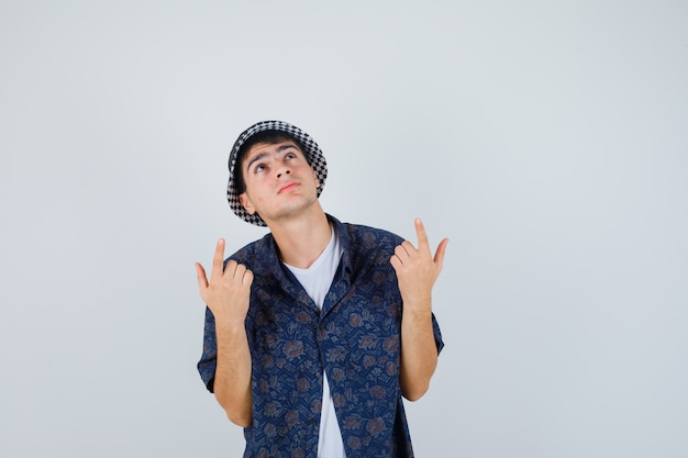 Young boy in white t-shirt, floral shirt, cap pointing up with index fingers and looking focused , front view.