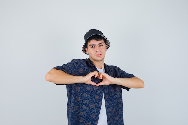 Young boy in white t-shirt, floral shirt, cap showing heart gesture and looking confident , front view.