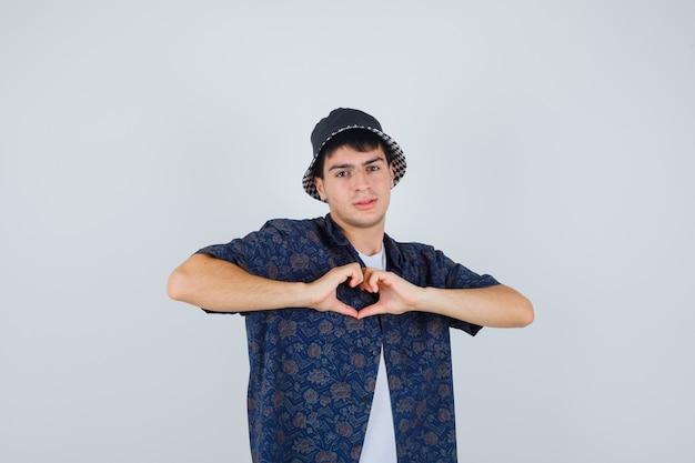 Giovane ragazzo in maglietta bianca, camicia floreale, cappuccio che mostra il gesto del cuore e che sembra fiducioso, vista frontale.