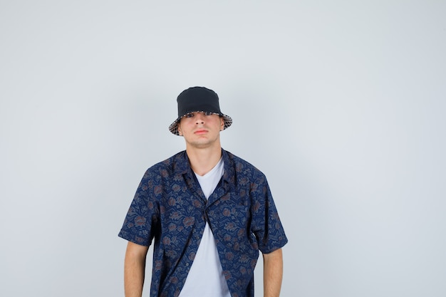 Young boy in white t-shirt, floral shirt, cap standing straight and posing at camera and looking confident , front view.