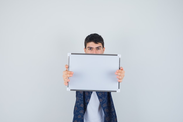 Young boy in white t-shirt, floral shirt holding whiteboard and looking serious , front view.