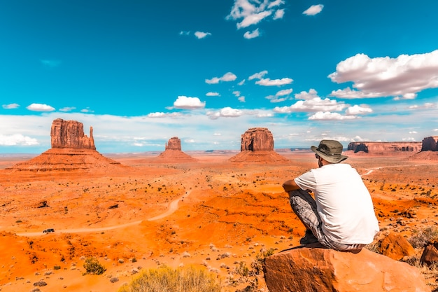 A young boy in a white t-shirt sitting to the right of the photo on a stone in the monument valley national park