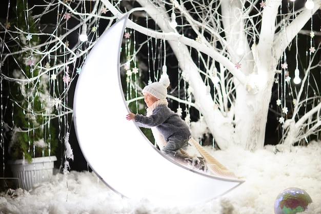 Young boy in winter hat, sweater and scarf climbing the white big toy moon in a magic forest with big white tree.