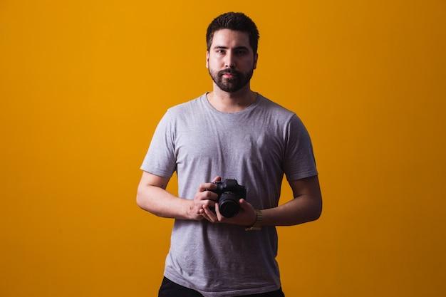 Мальчик с фотоаппаратом в руке. красивый фотограф на желтом фоне