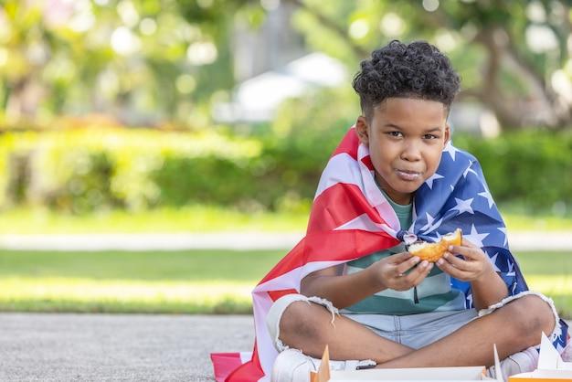 미국 국기가 달린 어린 소년이 7월 4일을 축하합니다.