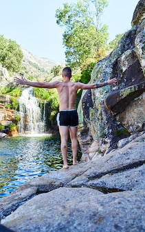 Young boy with arms crossed behind his back on a rock looking at the river with waterfall.