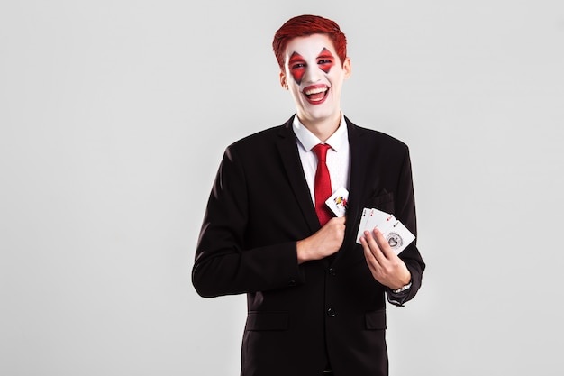 A young boy with an artistic make up joker . gamble and casino concept. studio shot. white background .
