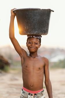 頭に洗面器を持つ少年