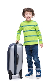Young boy with big suitcase before travel.