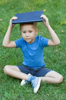 Young boy with a book on his head
